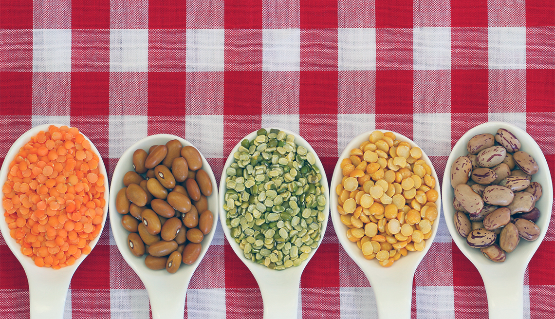 Selection of pulses on porcelain spoons on checkered tablecloth with copy space